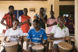 Three boys with drums are ready to start playing their instruments.