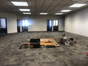 Basic emptied office space with three doors at the far end, a drop ceiling and gray carpet