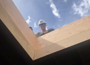 Sky light with man looking down in hard hat and blue sky with clouds