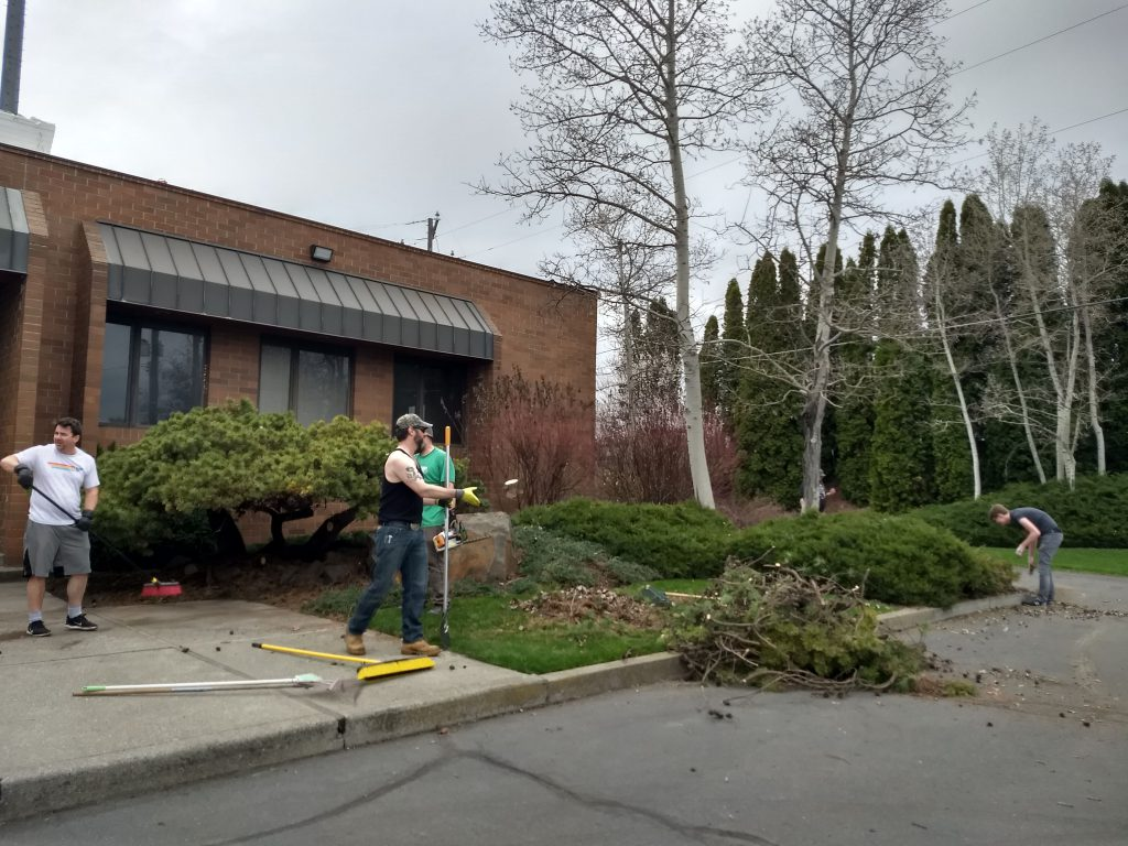 Four men with yard tools work to clean up the front yard area of a red brick business building