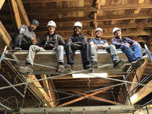 five smiling men in construction hats sit on the top of a scaffold and look down.