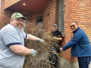 Three smiling men work to trim bushes and clean the yard in front of a red brick building