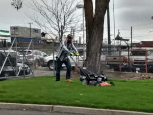 Man in baseball cap and wearing work gloves pushes a lawn mower.