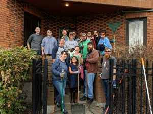 group of people all smiling with yard work tools standing on the steps of a red 2-story brick building
