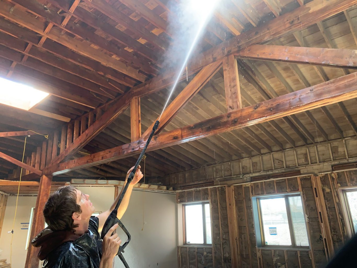 Worker blasts ceiling with water to remove old paint from trusses and rafters
