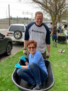 Mark Michaelis, smiling, pushes Stephanie Perko, also smiling, in a wheelbarrow