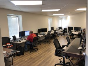 One man sits at a computer in an office room with computers on folding desks all around the walls of the space