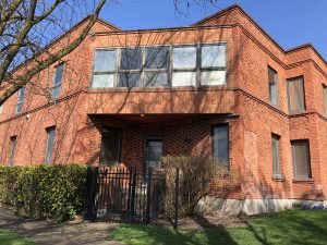 Old red brick 2-story building with gate to front door and newer addition built over entrance