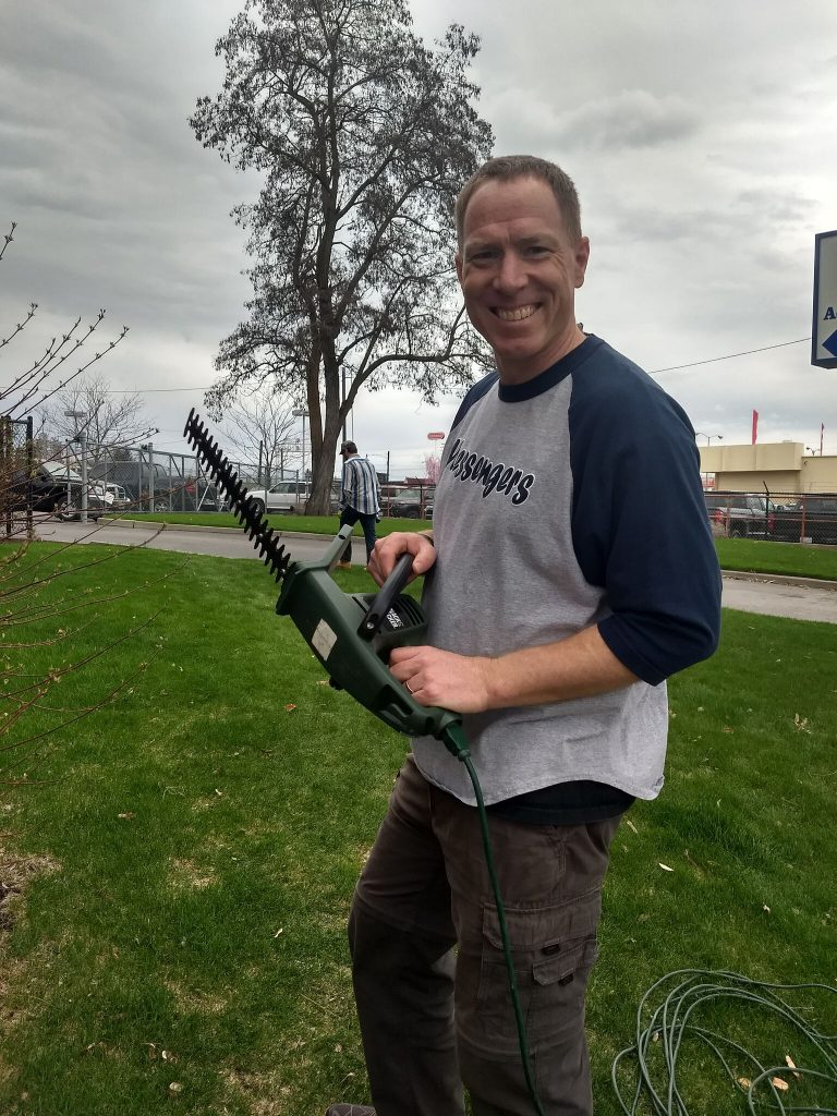 Smiling man shows off a hedge trimmer