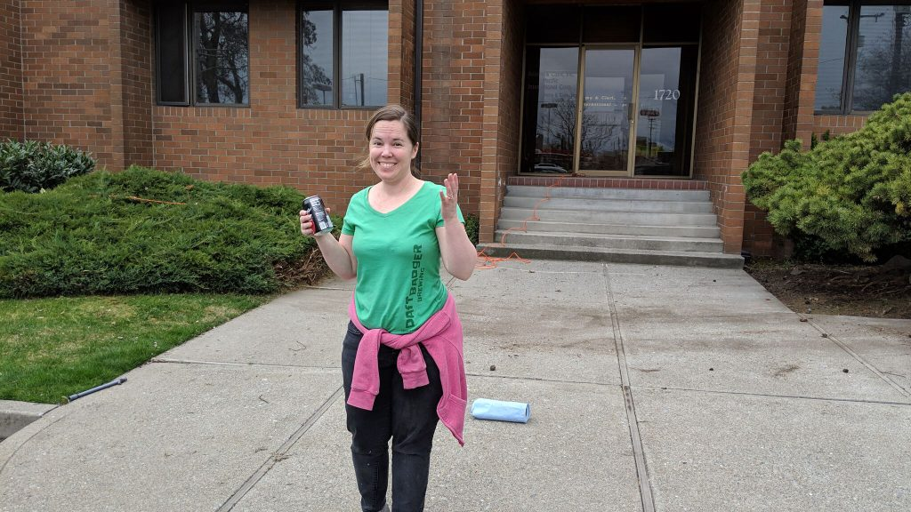 Woman smiles with hand raised and holding a soda can in front of a red brick office building