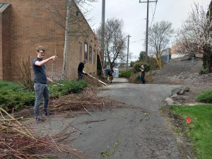 Four men doing yard work to clean up behind a red brick office building