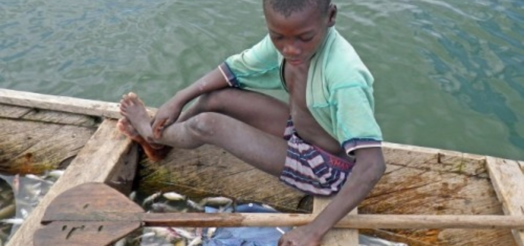pic of young african boy on a small boat.