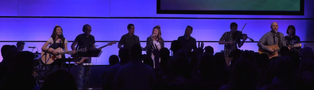 Picture of Grant and the worship team playing instruments and singing.