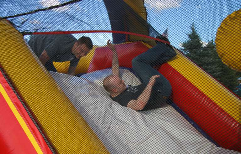 Two men falling down a slide as part of an obstacle course race at the IntelliTect company picnic