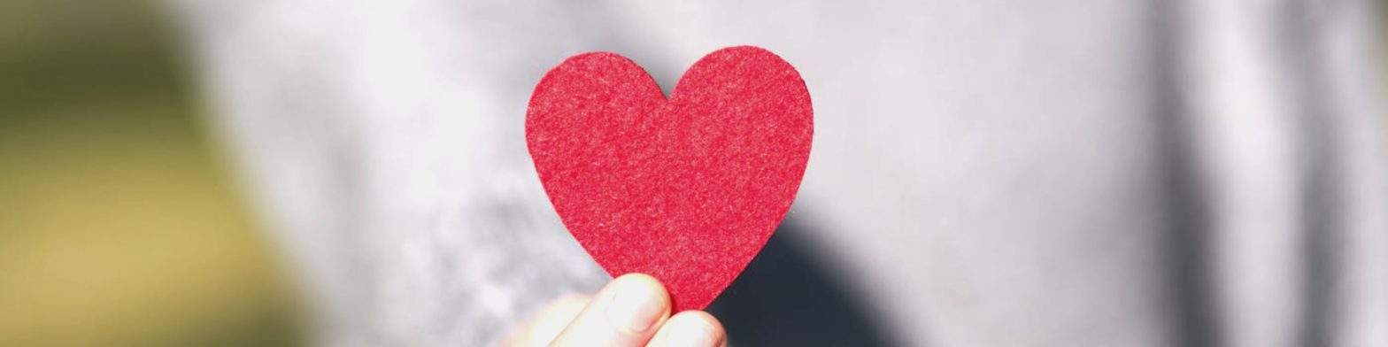 hand holding paper cutout of a red heart